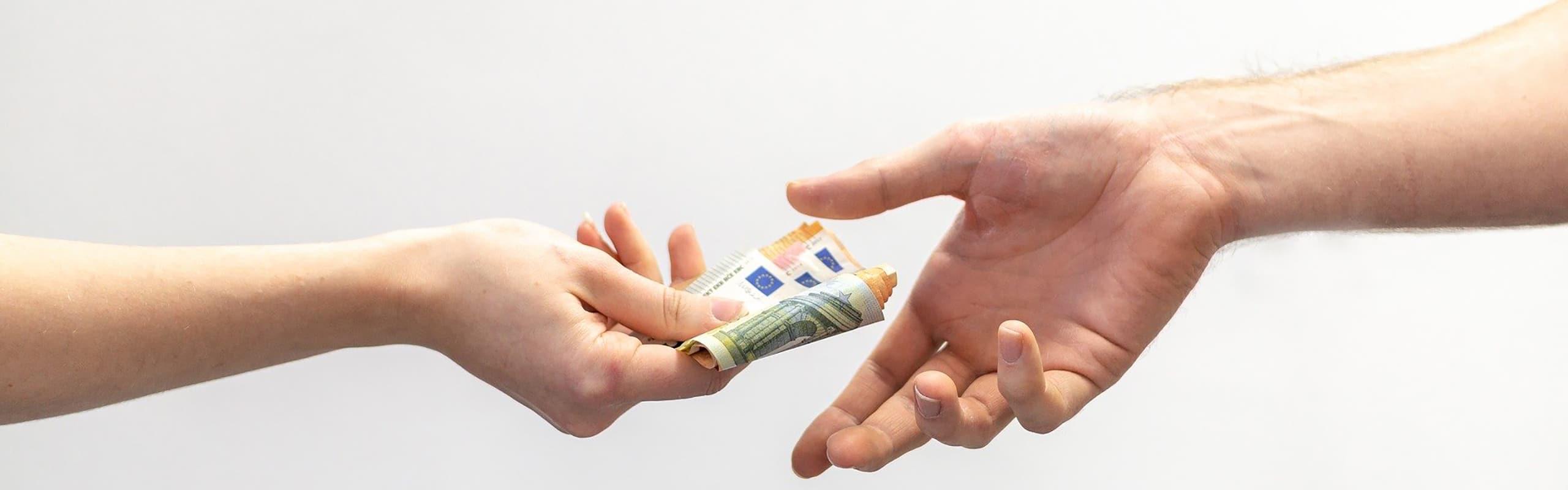 geld wird von einer hand in eine andere uebergeben