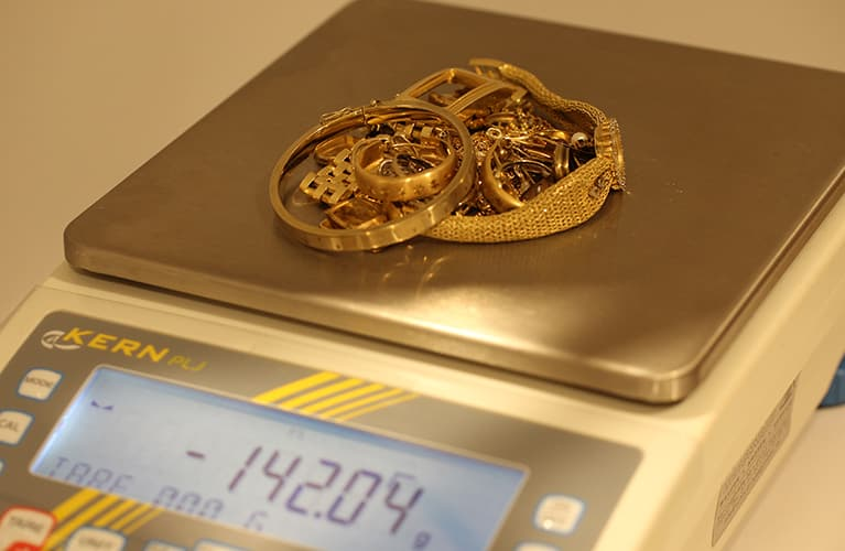 goldener schmuck auf einer waage mobil
